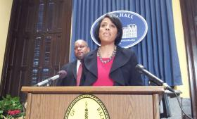 Mayor Stephanie Rawlings-Blake with City Transportation Director William Johnson (in background) following the Board of Estimates vote to pay Brekford Corporation $600,000 to get out of a contract to operate speed and red light cameras. Officials said the settlement allows the city to move forward in picking a new vendor to operate the cameras which have been offline since April.