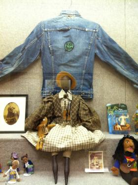 "Photos, dolls and a jacket adorned with a ""Black is Beautiful"" patch"