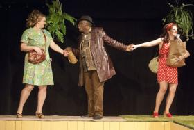 "In ""The Merry Wives of Windsor,""  set in the 1970s, ladies man John Falstaff tries to steal the hearts of wealthy married women to enrich himself. Actor Gregory Burgess is John Falstaff, with ""merry wives"" actors  Kate Michelsen Graham (left) and Lesley Malin (right)."