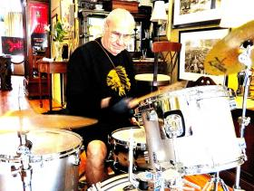 Bill Ward gives Aaron Henkin's drum kit a sound thrashing amidst the artworks and antiques of Annapolis Collection Gallery.