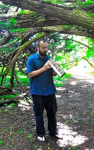 Composer Erik Spangler, playing melodica in the woods at Leakin Park