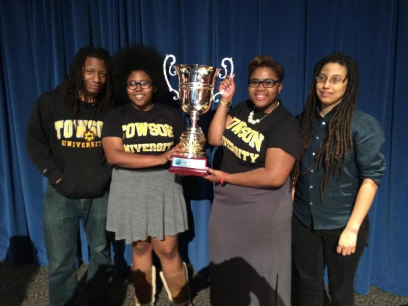 Left to Right:  Ignacio Evans, debate coach; Ameena Ruffin, Korey Johnson (holding cup); Amber Kelsie, debate coach.