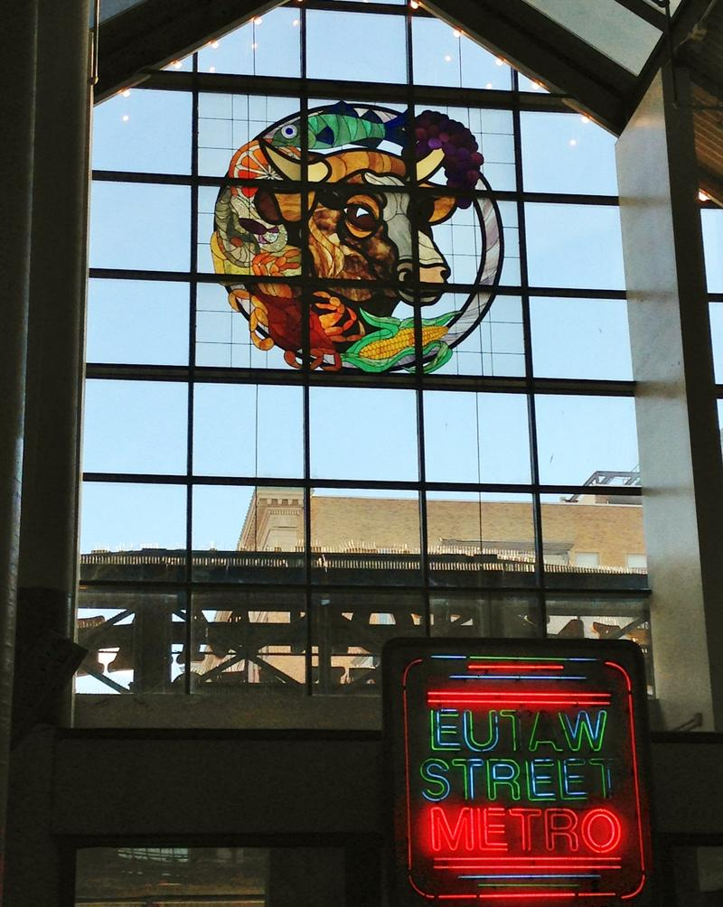 Above the entrance to Lexington Market, an iconic stained glass window depicts many of the market's offerings, such as beef, fish, seafood, and fresh produce.
