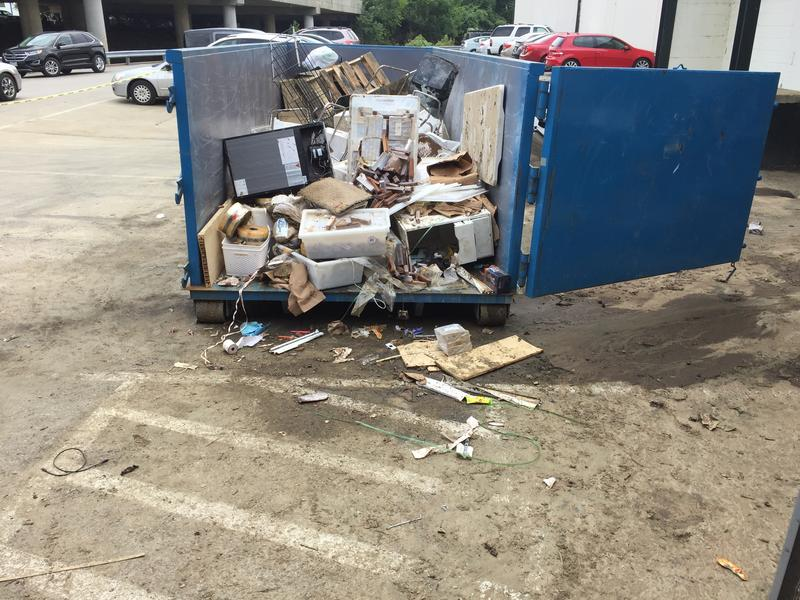 A dumpster for businesses to throw away items damaged by flood at Meadow Mill in Woodberry.