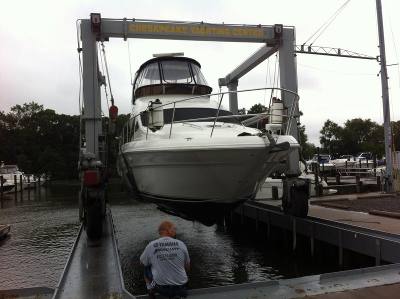 A boat is pulled from the water in the slings of a travel lift at the Chesapeake Yachting Center in Middle River