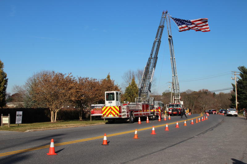 Fire trucks raise the American flag at the entrance to Dulaney Valley Memorial Guards, Suiter's final resting place.