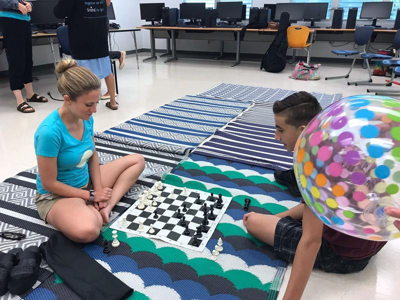 Angela Malley plays chess with a students at Camp Shine.