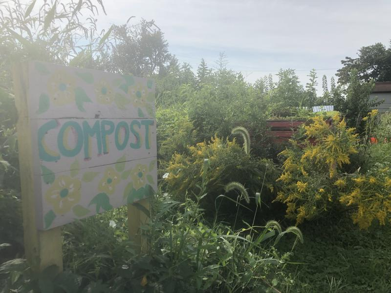 The compost bins sit in the back corner of the garden lot.