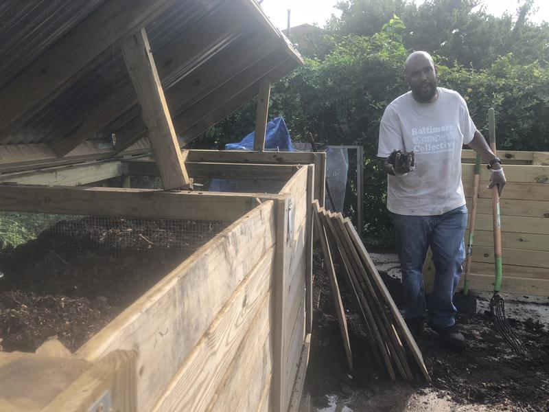 Marvin Hayes, the garden's manager, stands by the wooden containers each with three bins of the different stages of composting.