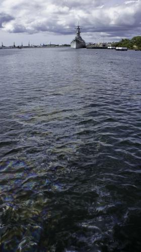 Shimmering oil leaking from the USS Arizona and flowing past the Missouri to the sea.
