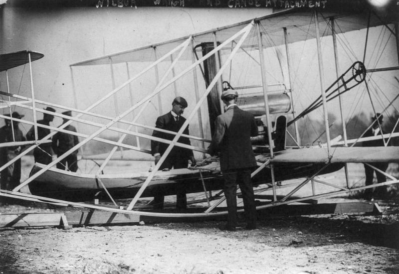 1909 Hudson-Fulton-Wright Flyer with canoe attached.  Wilbur and Charlie Taylor inspect the Flyer.