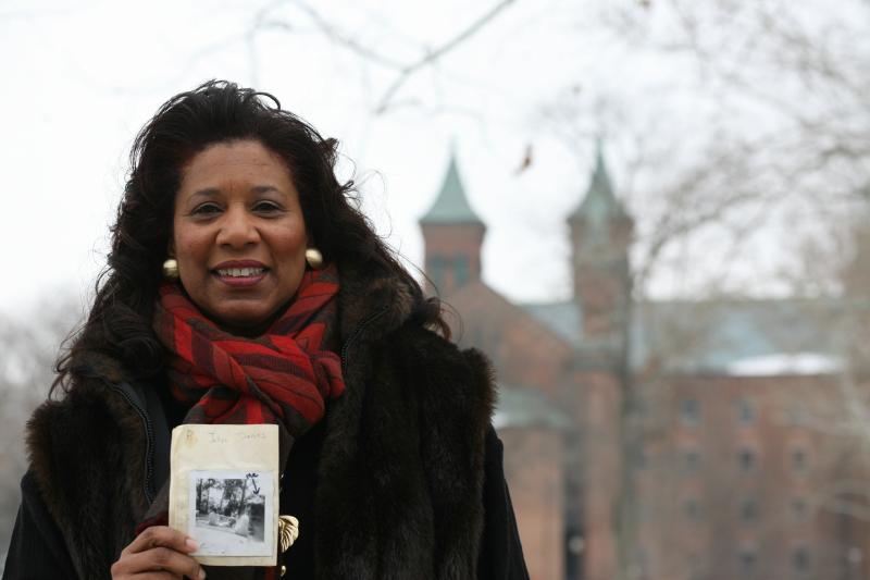 Jalyn Roe in front of the main building at Antioch College with a book she made as a child after hearing Dr. King's speech.