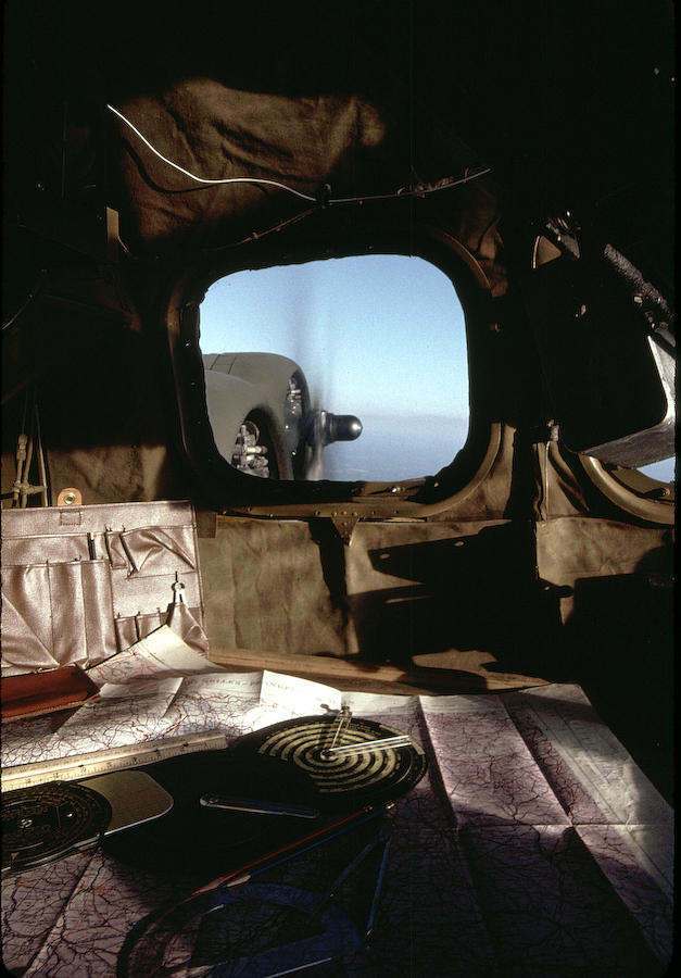 The tools of the navigator on the table for this crewman in the nose of the bomber, two of the Wright Cyclone engines turning just out the window.