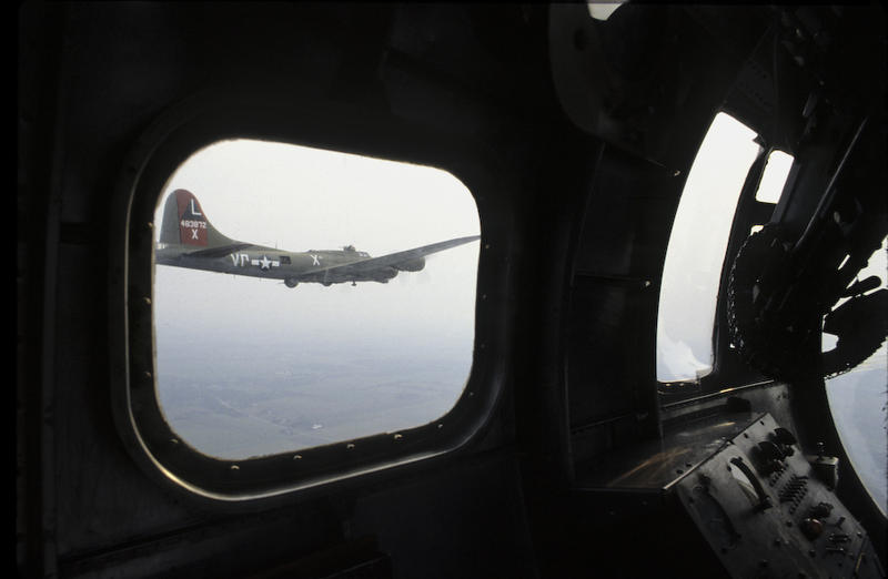 From the nose of a B-17 the navigators machine gun at left in the side window, the bombardiers control panel below, another B-17 in formation.