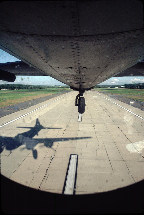 The B-17 roars off the runway into the sun, casting its own shadow on the runway.