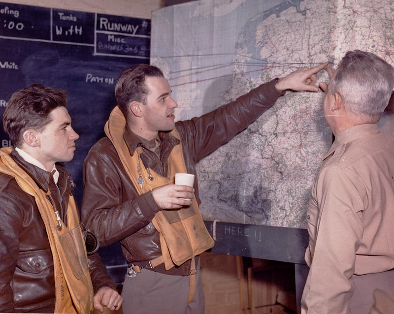 WW II P-47 ace Bud Mahurin (center) wearing an A-2 flight jacket while discussing a recent mission.
