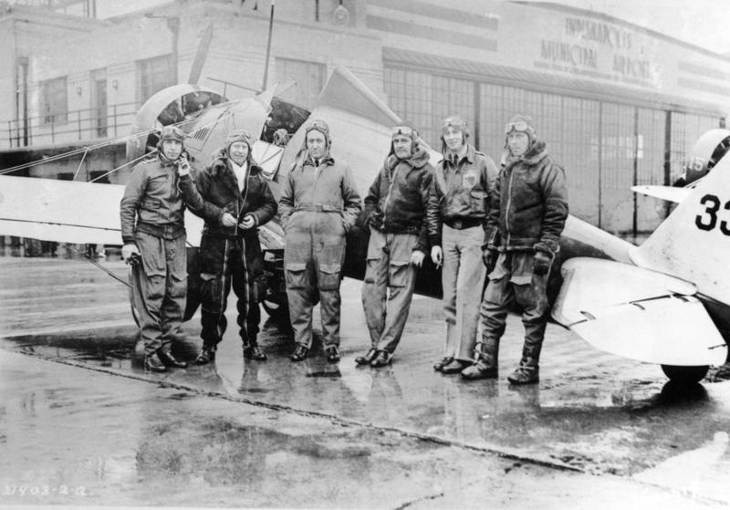 Army aviator Ralph Royce surrounded by fellow aviators wearing a variety of flight gear.