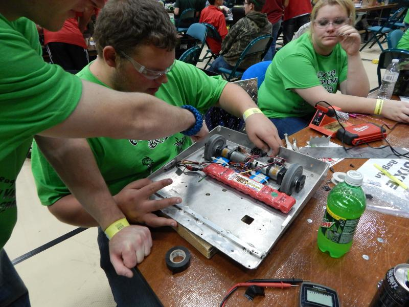 Troy Gabbard of New Lebanon repairs his team's robot.