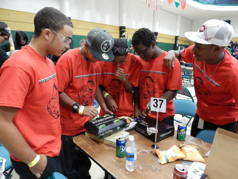 Members of the Mustangs, a team from Dayton's Ponitz Career Technology Center, lay low between matches.