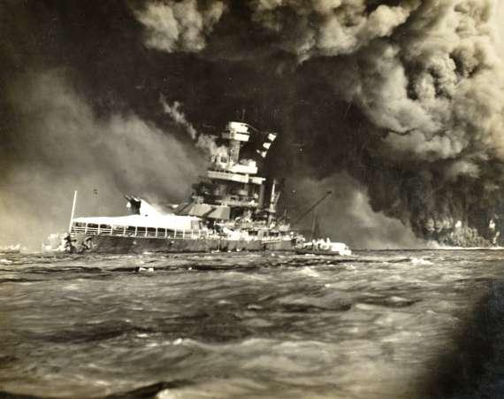 The sinking USS California in the foreground, behind the flaming Arizona.