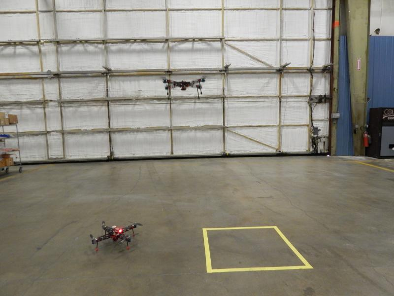 One drone looks on while the other one hovers in the hangar at SelectTech.