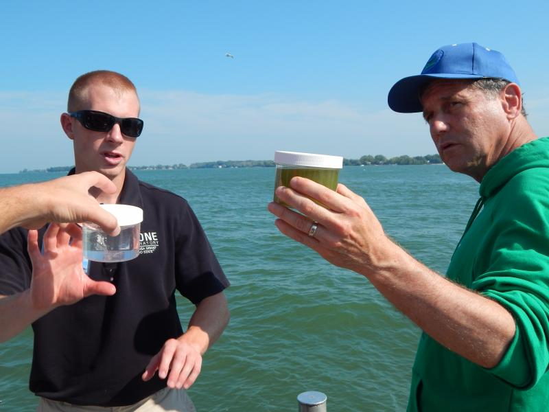 Senator Sherrod Brown (right) compared algae-filled water with clear water on a recent visit to Stone Lab on Lake Erie. Researcher Justin Chaffin is on the left.