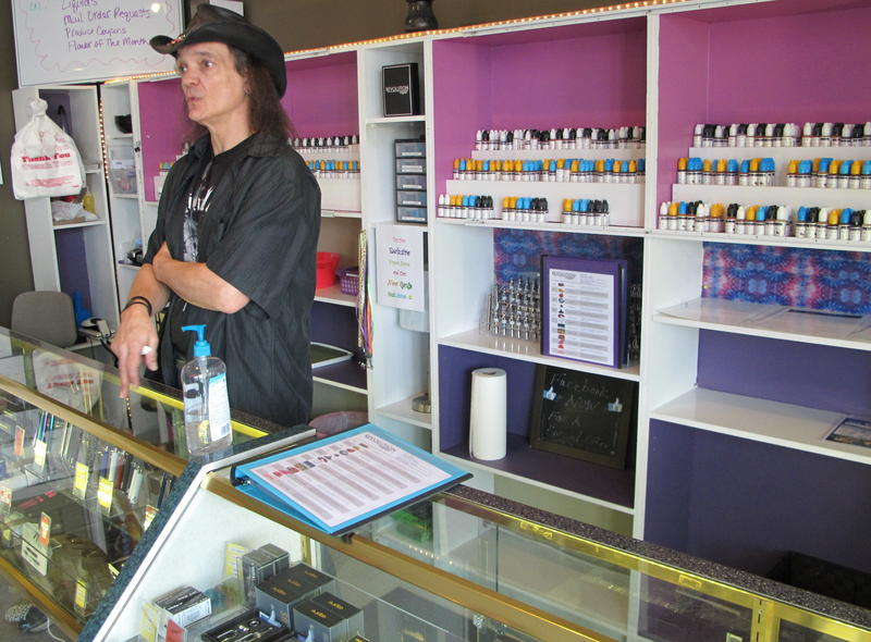 Vapor Shop employee John Talmage talks to customers. The price of the liquid nicotine used for e-cigarettes could triple under Gov. Kasich's budget proposal.