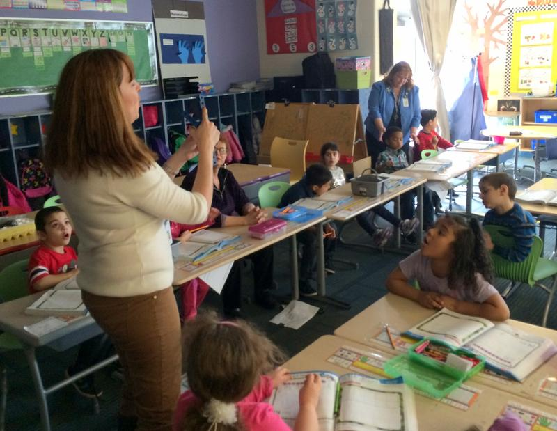 Kindergarten teacher Elizabeth Toomey is using cubes to help her students during a math lesson in Spanish.