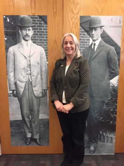 Dawne Dewey stands next to life-size murals of Orville and Wilbur Wright.