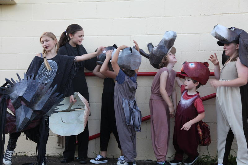 "Left to right: Maggie Knopp, Amelie Maruyama, Merida Kuder-Wexler, Mateo Basora, Lucy Dennis, Oskar Dennis, and Kira Hendrickson wait to go onstage for a run-through of ""The Farm"" at the Amphitheater in Yellow Springs."
