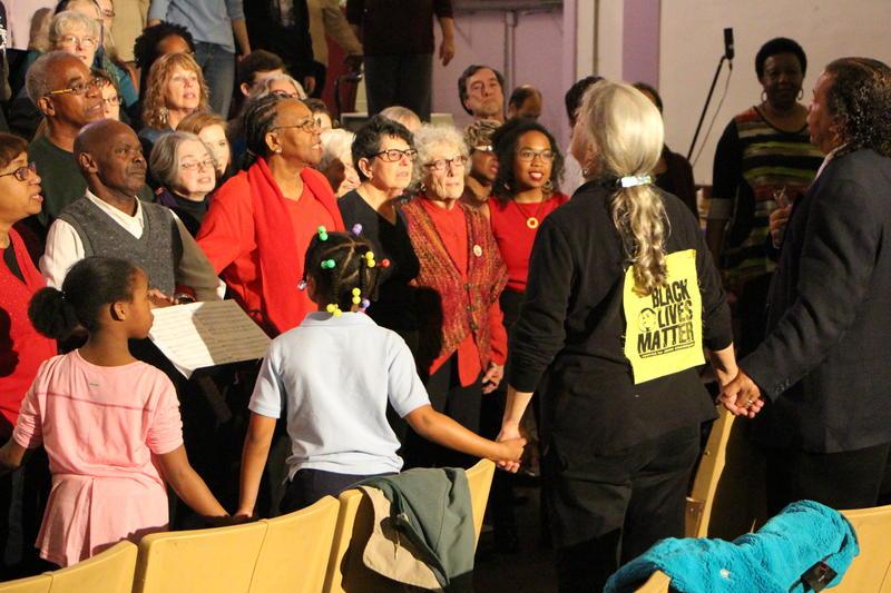 Cathy Roma directs a choir performance in Cincinnati.