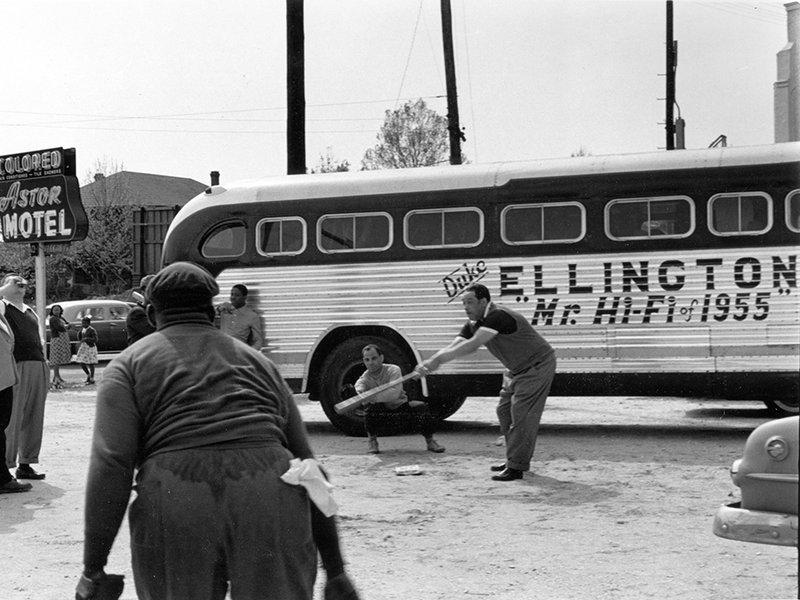 "Duke Ellington and band members playing baseball in front of their segregated motel (""Astor Motel"") while touring in Florida."