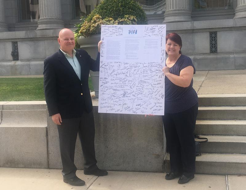 Heath McAlpine and Mary Ramey of Dayton Indivisible For All pose by the letter addressed to Representative Mike Turner