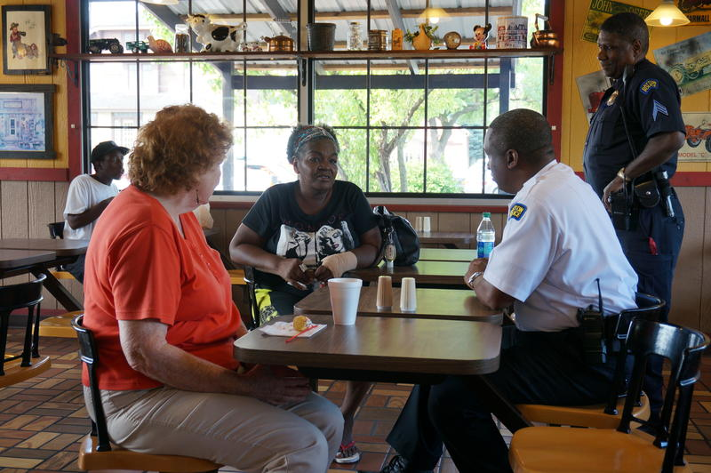 Dayton residents chat with police during a Coffee With a Cop event at Benjamin's the Burger Master.