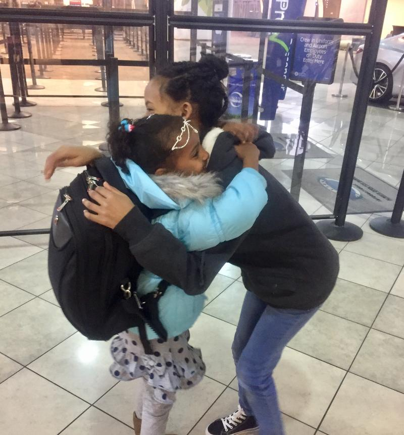 Zula, 13, and her niece Semira,7, embrace after she arrives at the airport.