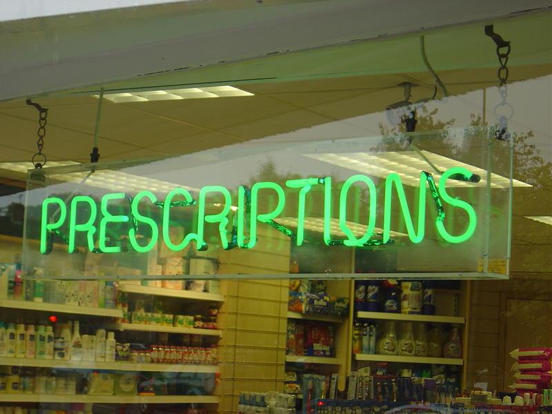 green prescription sign in pharmacy window