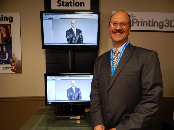 Vandalia Vice-Mayor Mike Blakesly next to a 3D scan of himself. The scan will be turned into a digital model for a 3D printer that creates tiny, full-color replicas.