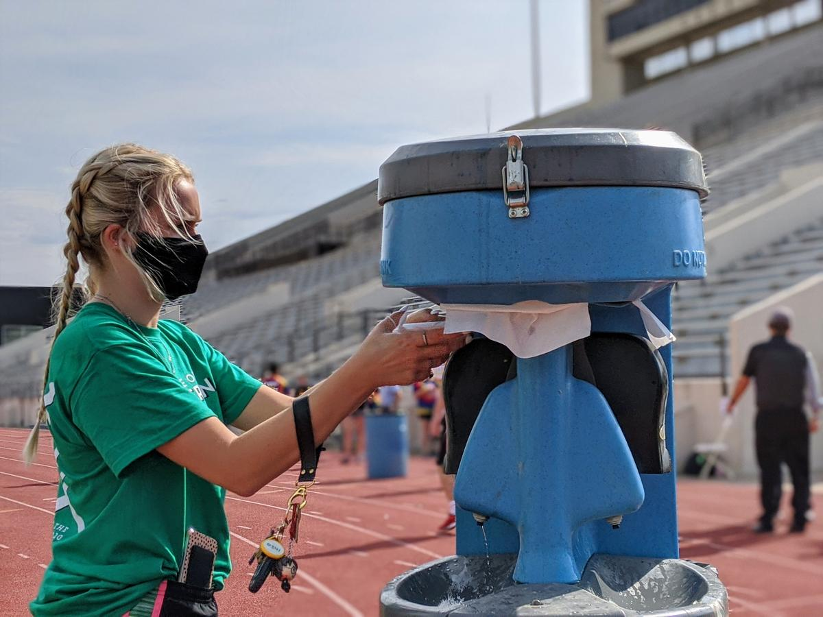 Students were required to wash their hands before taking and leaving the field during Wichita State University's Clash of the Colleges. (Photo by Stephan Bisaha, Kansas News Service)