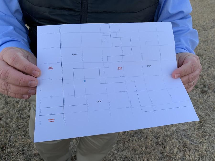 Joey Bahr holds a map that shows how close his home is (represented by a blue dot) to a neighboring internet service area that offers cable broadband. (Photo by David Condos, Kansas News Service)