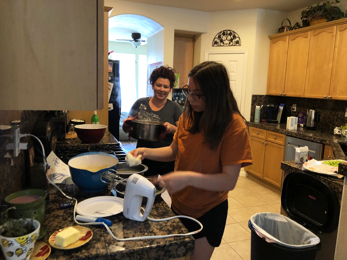 teenager cooks in kitchen with mother