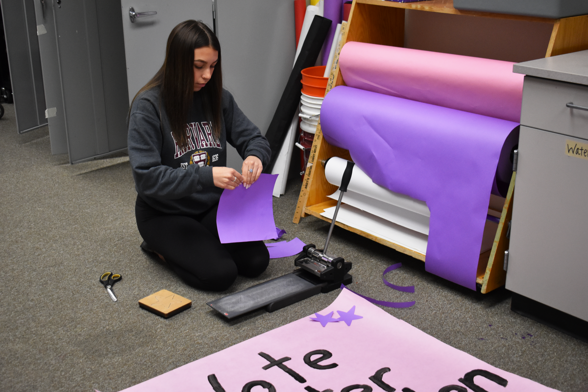 Teen cuts out purple stars to paste on her peers' campaign poster