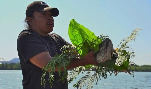 A file photo of a member of Puget Sound's Swinomish tribe participating in a ceremonial salmon blessing. Northwest tribes hold vigils along the Columbia River to pray for the return of salmon.
