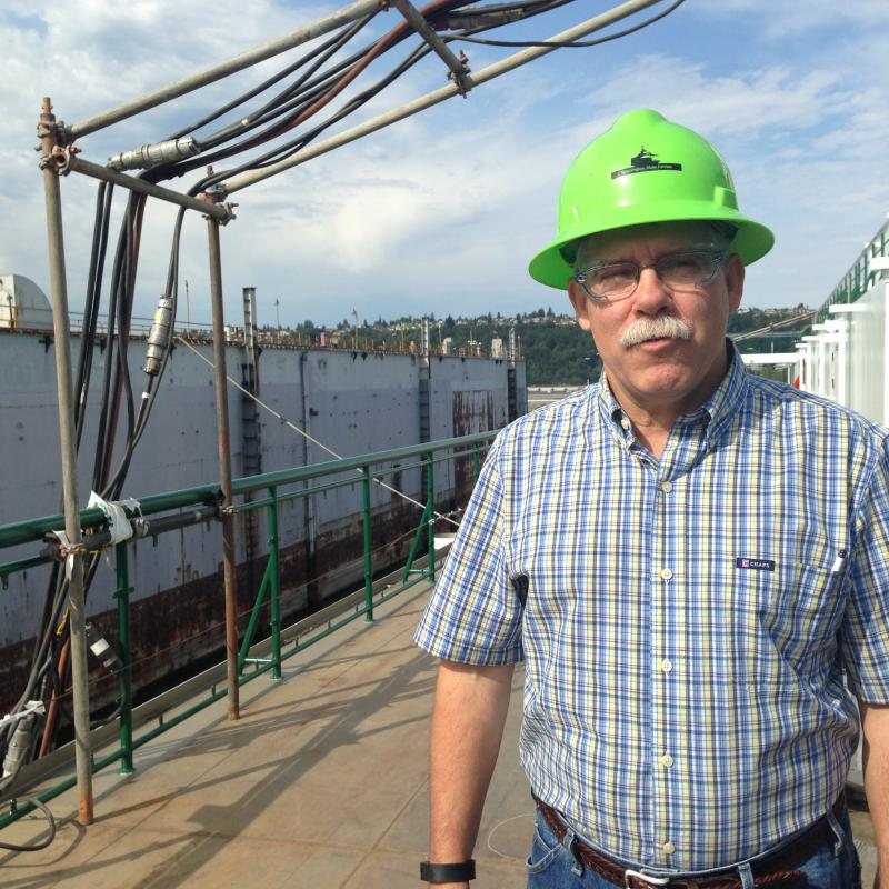 Samish project manager Dave Visneski, on the deck of his ferry. A drydock - a floating holding area for a ship needing repairs - is in the background.