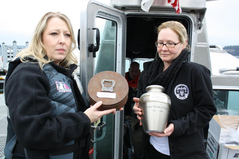 Amber Larkins and Terry Jaeger of the Pierce County Medical Examiner's office hold up vessels containing unclaimed cremated remains.