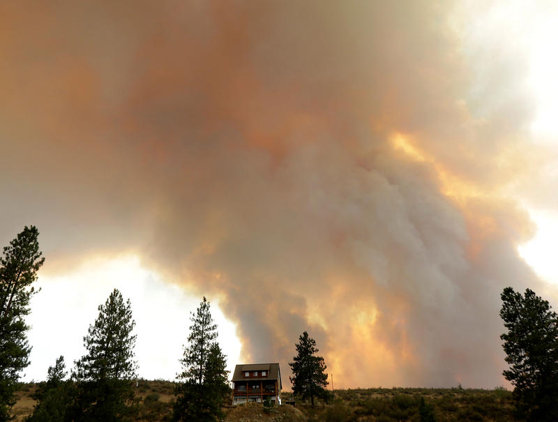 Smoke from an approaching wildfire looms over a home near Twisp, Wash., Aug. 19, 2015.