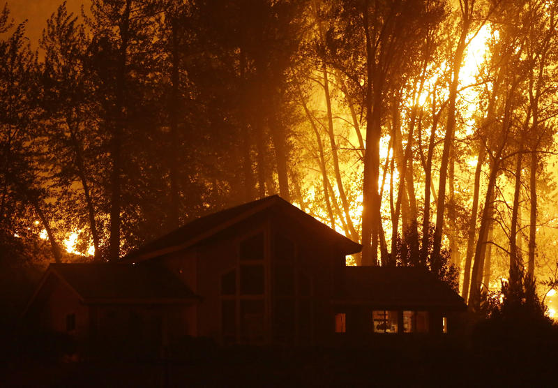 A wildfire burns behind a home on Twisp River Road early Thursday, Aug. 20, 2015 in Twisp, Wash.