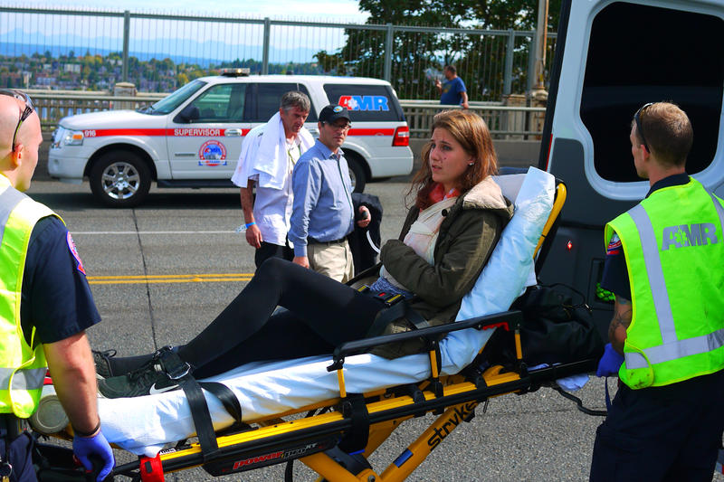 A woman is taken to an ambulance on the Aurora Bridge after the crash Thursday.