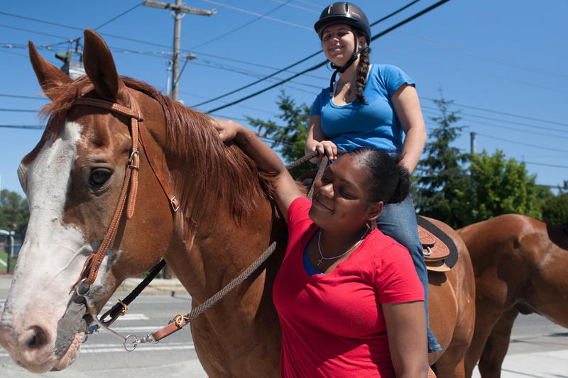 Riley Neiders and her horse Homer attract the attention of Rainier Beach resident Lamaya Barron.
