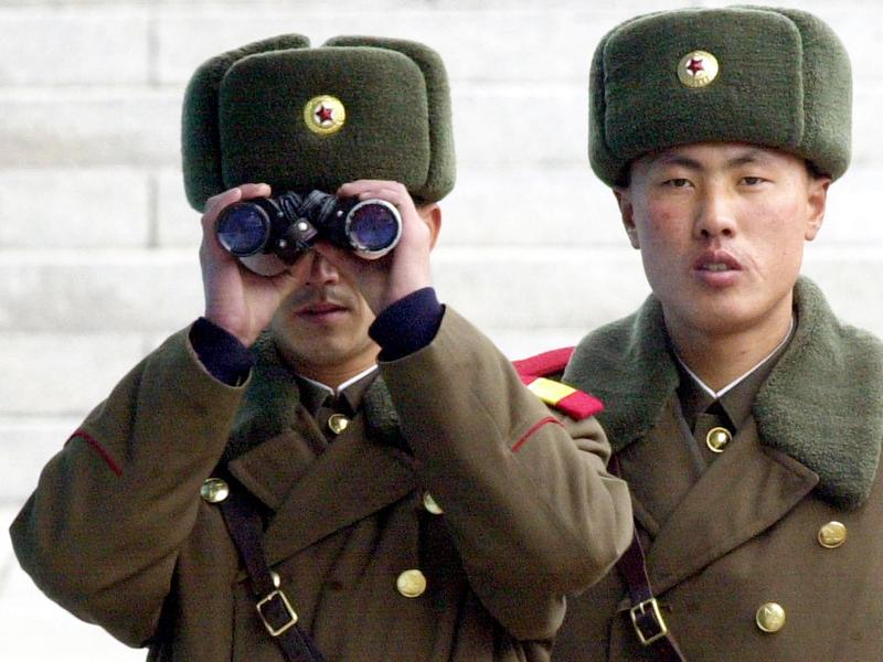A North Korean soldier looks at the southern side through a pair of binoculars at the border village of Panmunjom, north of Seoul, Wednesday, Feb. 26, 2003.
