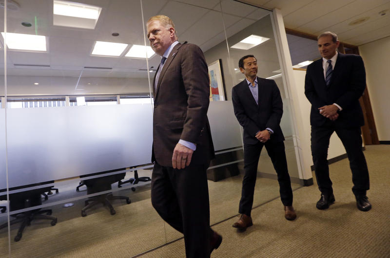 Seattle Mayor Ed Murray, left, walks past his husband, Michael Shiosaki, center, and his attorney, Bob Sulkin, to make a statement to media members Friday, April 7, 2017, in Seattle.